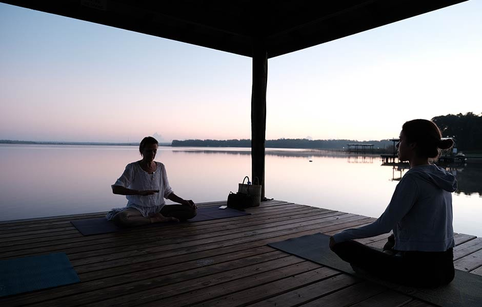 Morning meditation guidance at the pristine lake during a wellness retreat at the Amrit Yoga Institute