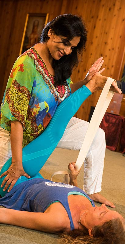 Kamini Desai demonstrating a yoga therapy stretch using straps to assist the client